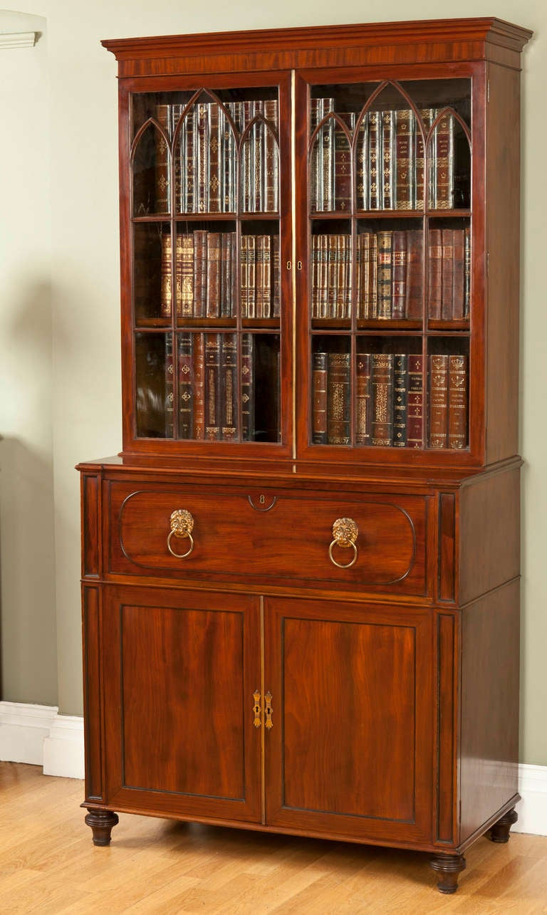 The rectangular moulded cornice above a plain frieze and a pair of glazed gothic-arched doors enclosing three adjustable shelves, the lower section with panelled secretaire drawer: the hinged flap enclosing a leather lined writing surface and a