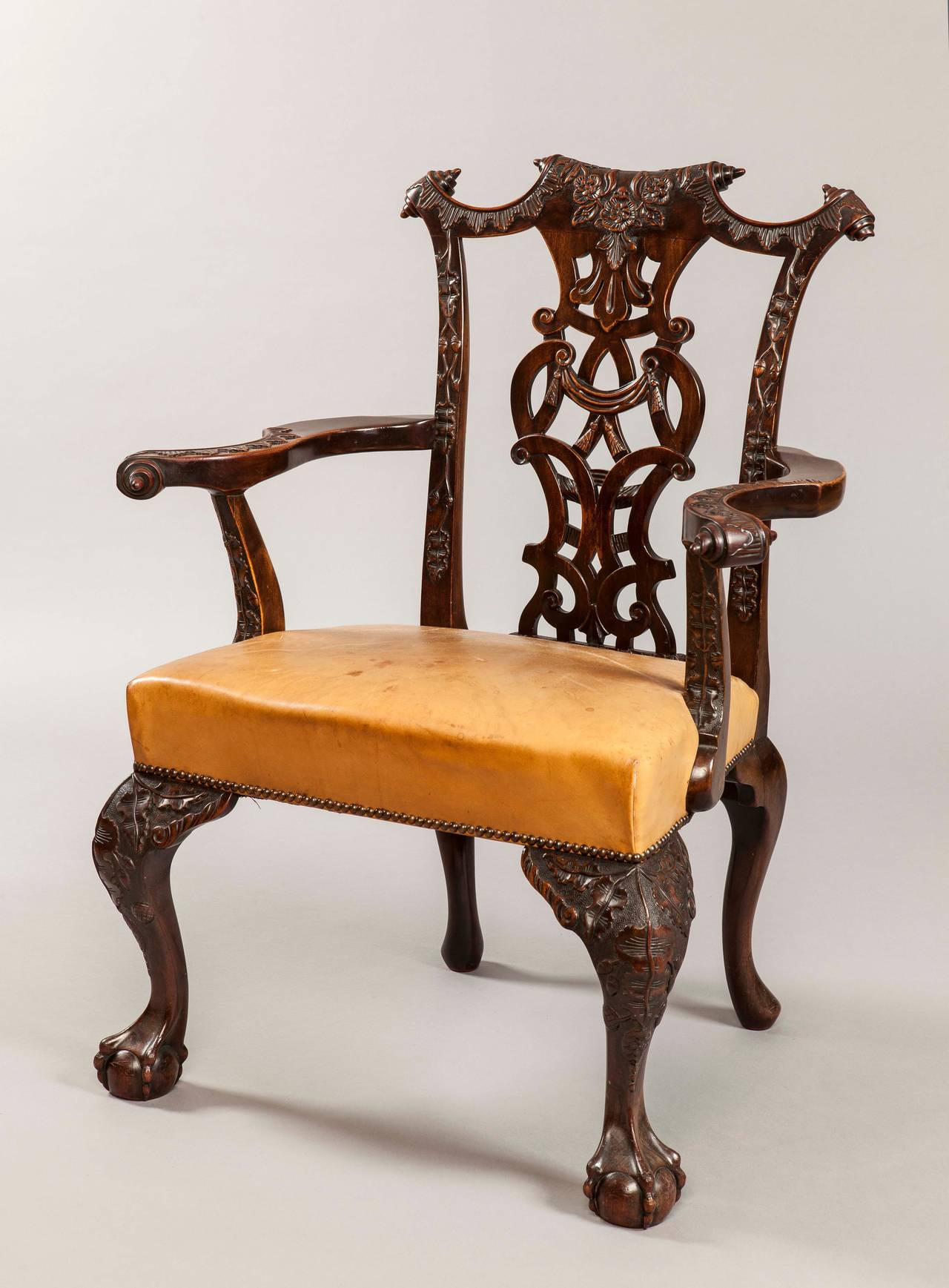 Comprising 12 chairs, and consisting of two Carver armchairs, and ten side chairs; constructed in mahogany, which has been excellently and comprehensively carved; rising from cabriole front legs, with ball and claw feet, having foliate carved knees