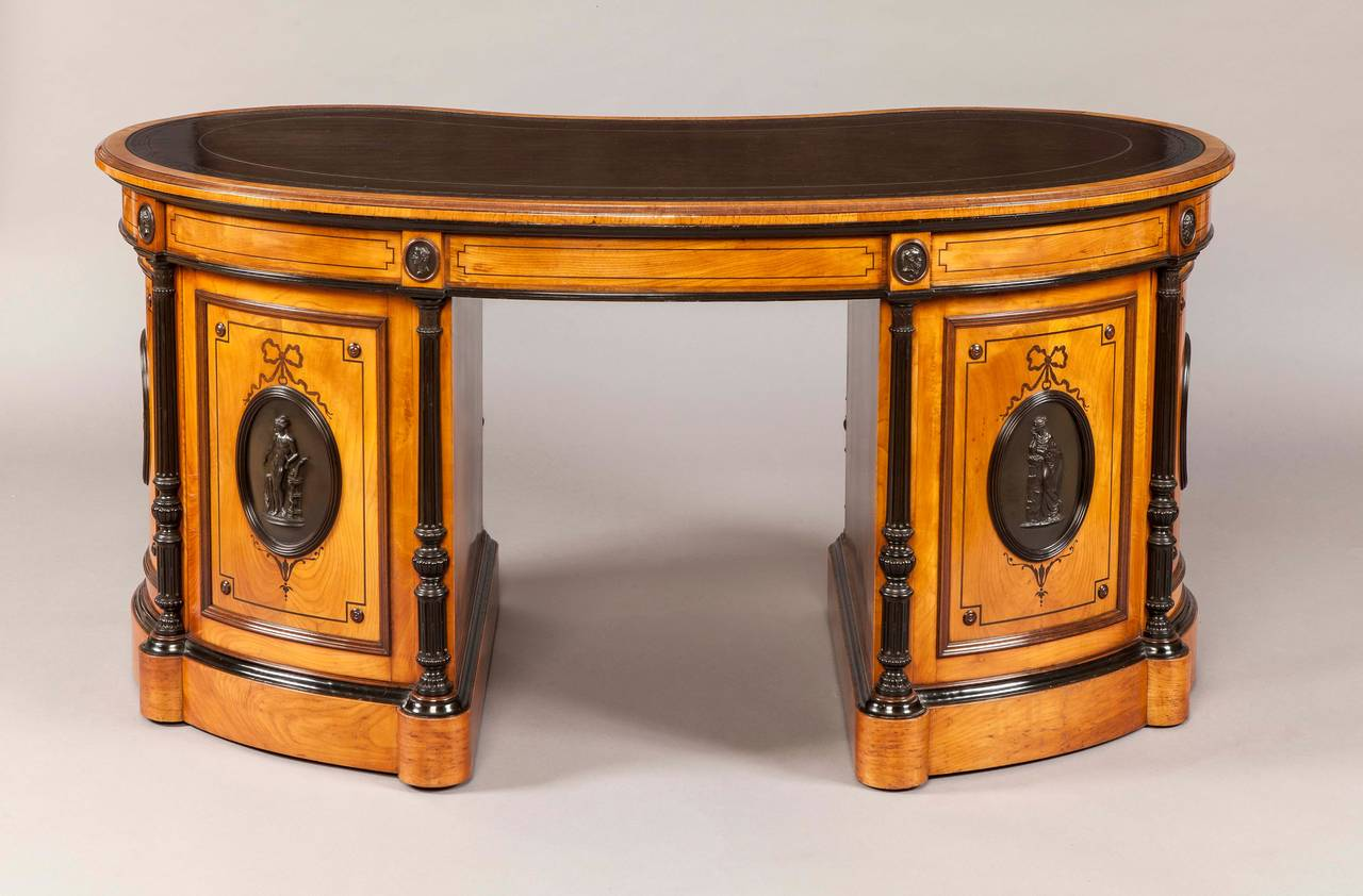 A rare kidney shaped desk by Wright & Mansfield.  Of freestanding form, constructed in gean wood (Highland Black Cherry), dressed with fourteen Wedgwood black basalt plaques of Antique figures (stamped Wedgwood to the rear) and decorated with