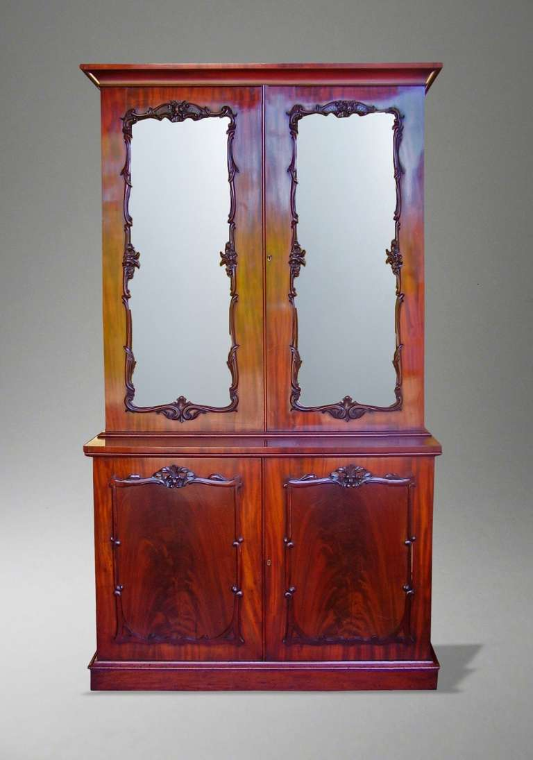 A fine two-door bookcase  Constructed in a fine mahogany, with flame veneers to the front; rising from a plinth base, the lockable blind doors over having recessed fielded panels with a well carved serpentine trim, enclosing a shelved interior;