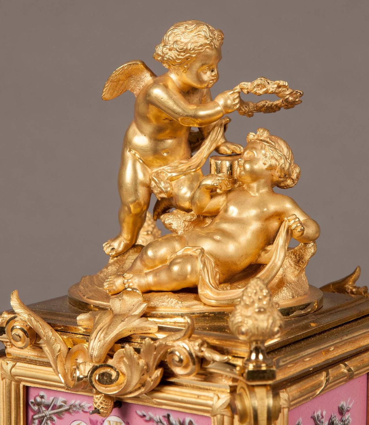 A carriage clock in the Louis XV manner  The ornate and shaped gilt bronze case having putti at the angles, surmounted by two winged putti, one proffering a laurel wreath; dressed with hand painted dusky rose 'Sevres' hand painted panels framed