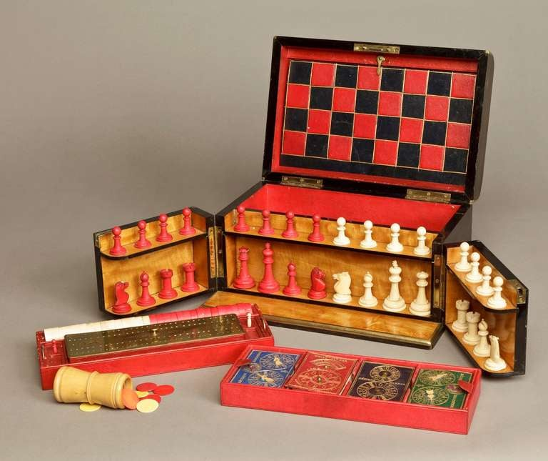 The domed case constructed in a well marked Coromandel, with protective brass guard strips, having a rising and lockable lid and a gated front, with a Satinwood interior, revealing the games, which include Chess, Draughts, Bezique, Whist and