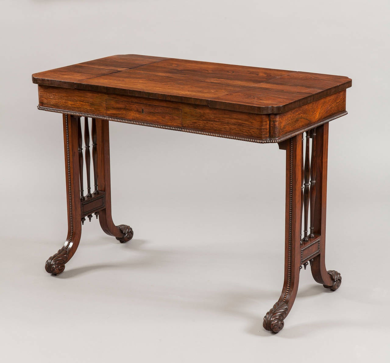 Constructed in a finely figured goncalo alves; the end supports having square uprights, each enclosing three tapering and turned 'triple spindles', with 'running pearl' adornments, and terminating in incurving carved scroll toes; the platform having