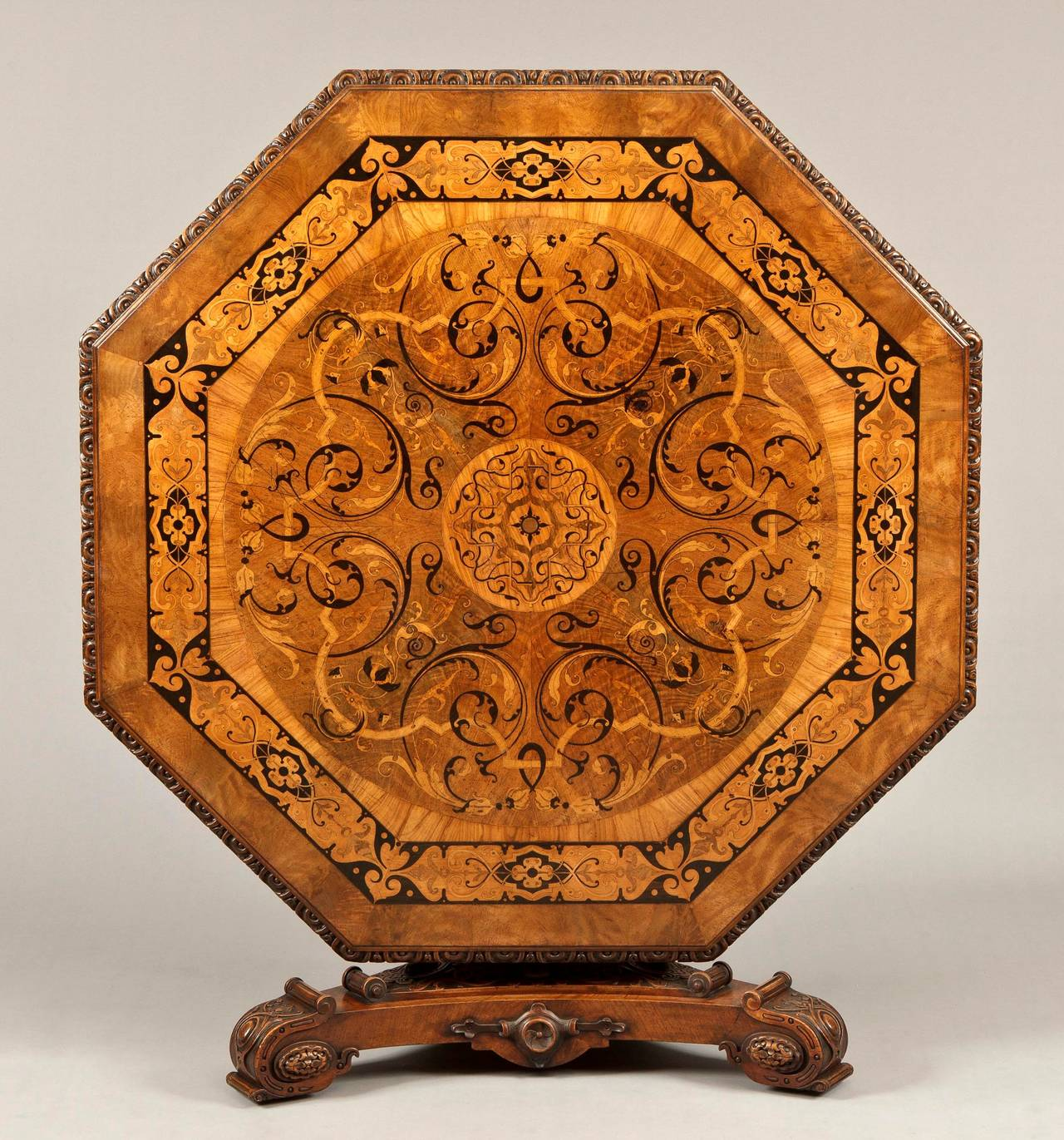 An outstanding centre table labelled James Winter & Sons,  Wardour Street, London Of octagonal form: constructed in a finely marked Circassian walnut, carved, and with arabesque inlays in primarily ebony, and specimen woods; the tripartite