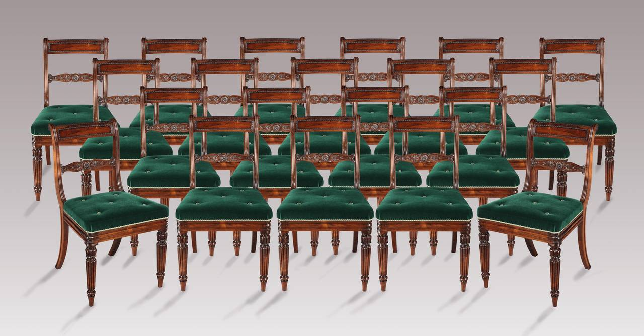 Constructed in a finely figured and beautifully patinated goncalo alves: the twenty chairs, consecutively numbered in Roman numerals to the frames, from One to Twenty, rise from gently tapering front legs, turned, lobed and carved with inverted