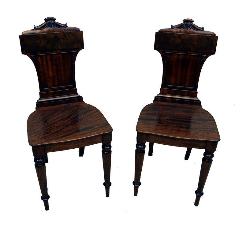 A Pair Of Regency Mahogany Hall Chairs Of Unusual Design Having Shaped And Carved Backs Above Well Figured Shaped Seats Standing On Elegant Turned Legs.