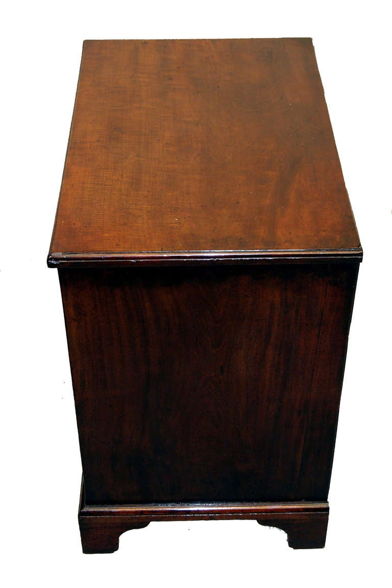 An 18th Century Mahogany Kneehole Desk Of Superb Colour And Patina The Rectangular Top With Moulded Edge Above Arrangement Of Drawers Flanking Recessed Central Cupboard Door With Original Brass Throughout Standing On Original Shaped Bracket Feet.