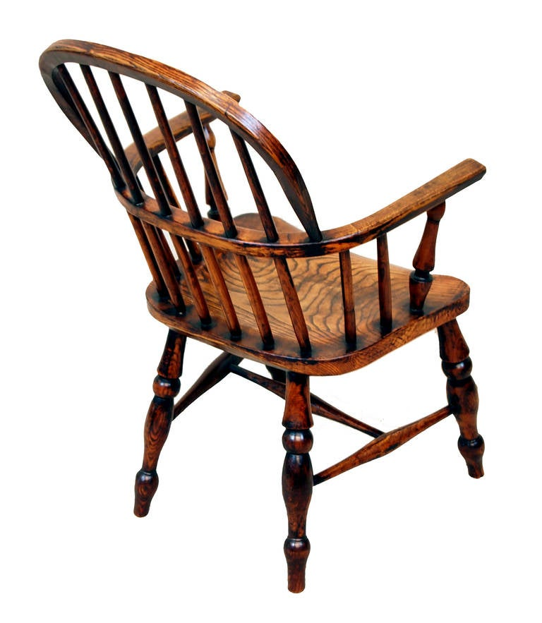 A delightful mid-19th century ash and elm child's Windsor chair having attractive stick back with turned arm supports above well figured and shaped seat raised on elegant turned legs and H stretcher.