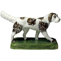 Antique pottery figure of a setter dog standing on a base