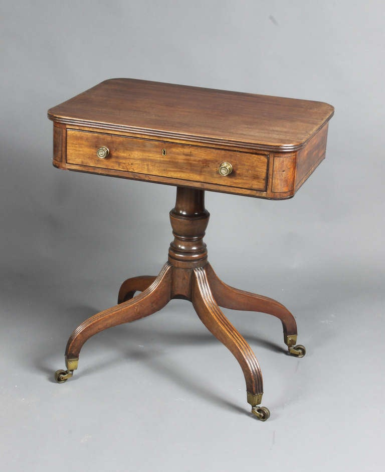 A good Regency mahogany occasional table or writing table on a four-splay base. The drawer pulls out and the top hinged section slants for writing on; there is also a small ink drawer