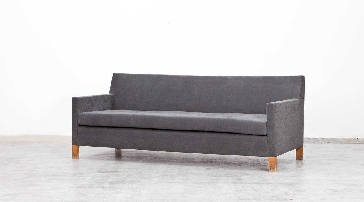 This sofa was designed by German architect Ferdinand Kramer in 1953 for Johann-Wolfgang-Goethe University in Frankfurt am Main. Its straight lines and generous proportions convey a composed and inviting character for the upholstered sofa, thus