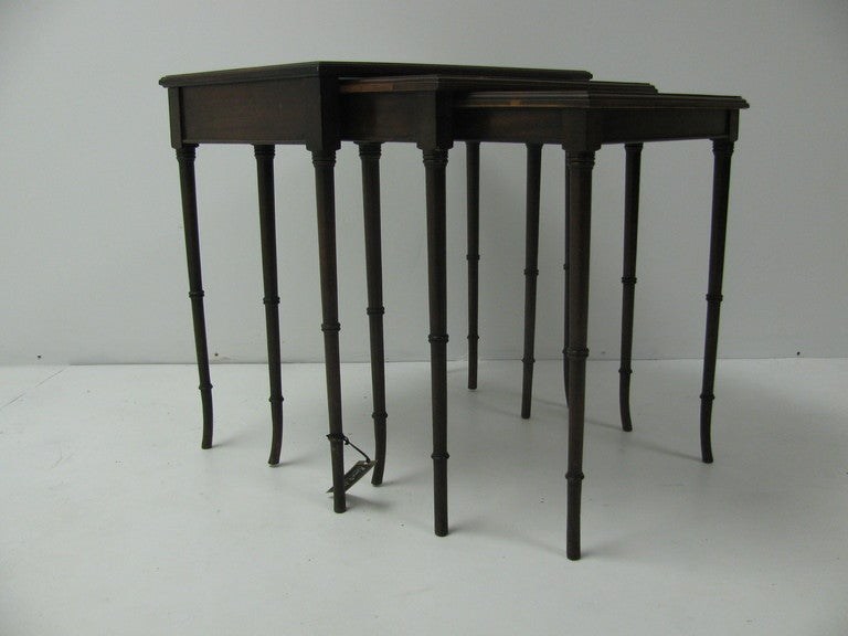 Set of three faux bamboo mahogany tables. Legs taper and flare at bottom. Larger table has a black glass top.