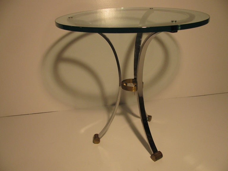 Nickeled chrome tables with a tri-leg design. Legs are connected to a chromed band that dimensional glass top is attached to. At the middle where legs splay is a brass ring and three balls securing legs. Brass cylinders comprise the feet. Very