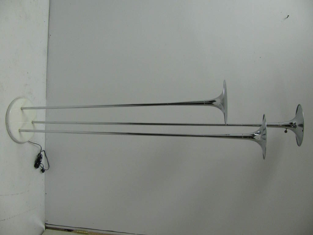 Horn styled floor lamp by Reggiani. Three separate flared sections of trumpet like nickel chrome steel. Three way switch.