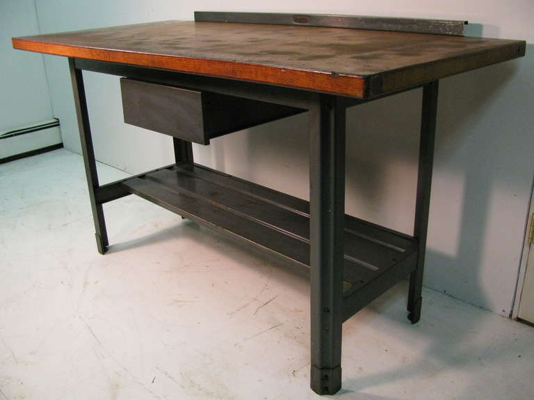 Wood top with steel frame, gallery and drawer. Great for a desk or a kitchen work table. Table is originally from a NYC machine shop which built elevator parts. Gallery back splash can be removed so table can be accessed from all sides.