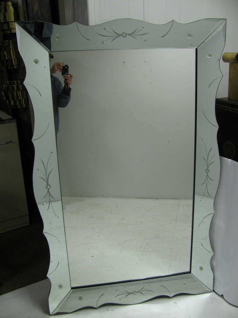 Beautifully executed mirror with scalloped and reverse etched panels. Measure: Large size 66 x 42, gives it command of a wall.