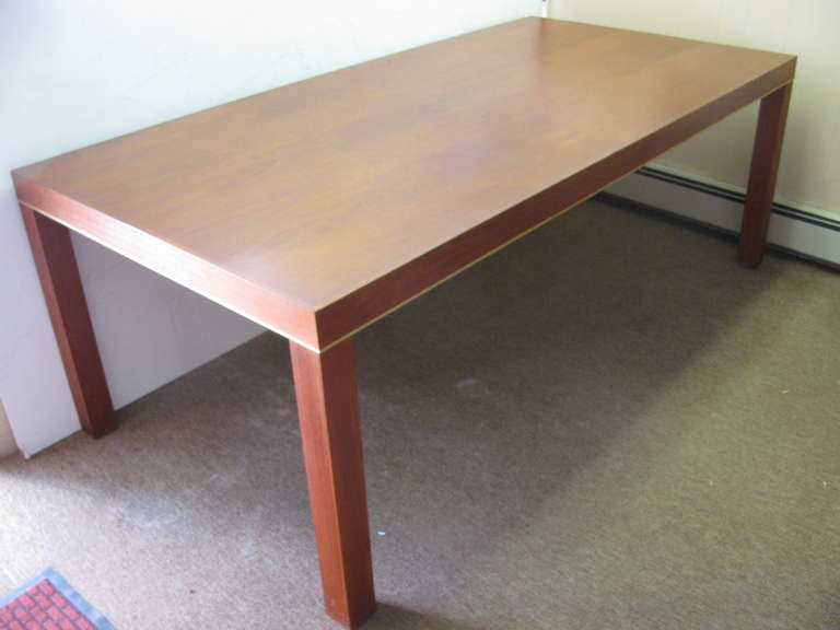 Elegant large teak dining table with brass detail accenting the apron. Table is seven foot long by three and a half wide. Simple design with square legs at the corners. A great value, possibly a Baughman table design.