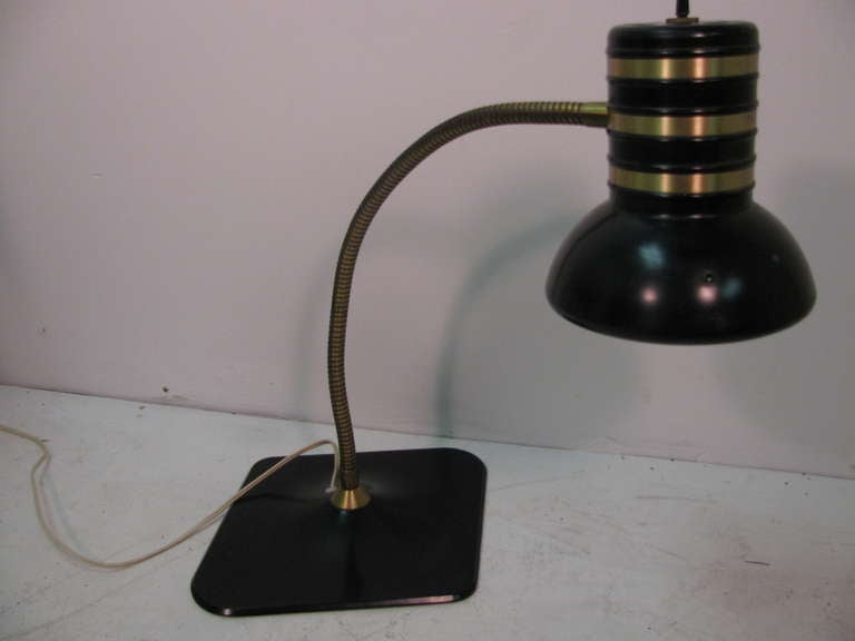 Rare form desk lamp by The Dazor Mfg. Corp. Bands of brass circle shade. Enameled steel with brass flexible pivoting arm. Height is 20.5 with shade downwards, and at max height. This item can be parcel posted.