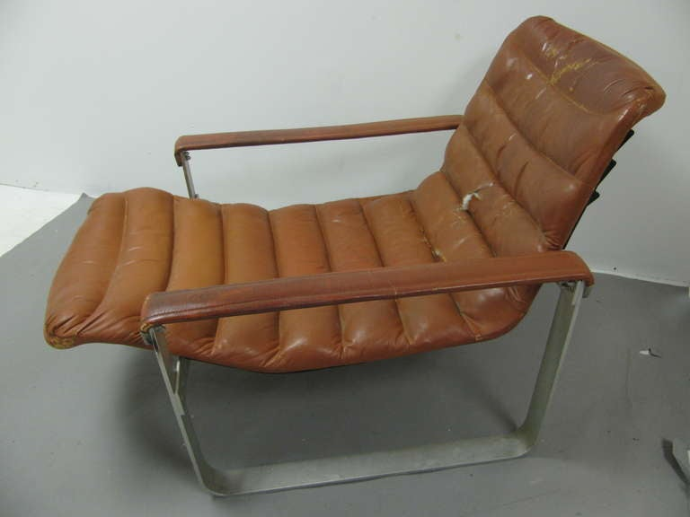 Fabulous form and comfort. Designed by Tapiovaara, circa 1962. Rigid aluminum chair frame has three positions, seat lifts off frame for repositioning. Arms have flexibility, and are covered in leather. Ottoman size 22 W x 20 L x 12 H, and is