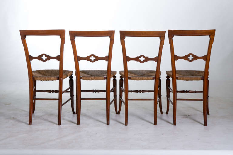 A set of four 19th century English Gothic dining chairs with rush seats and delicately tapered legs. The finish on the chairs is original. The back leg of one chair (see photographs) has been repaired. The chairs are sturdy and can be used for