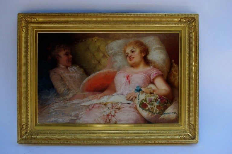 Framed oil on canvas representing two women in a couch. The right one is dressed in sweet pink and comfortably sat on wide pillows, a open book on her knees. Her friend is holding a red range and both of them are laughing, maybe because of their