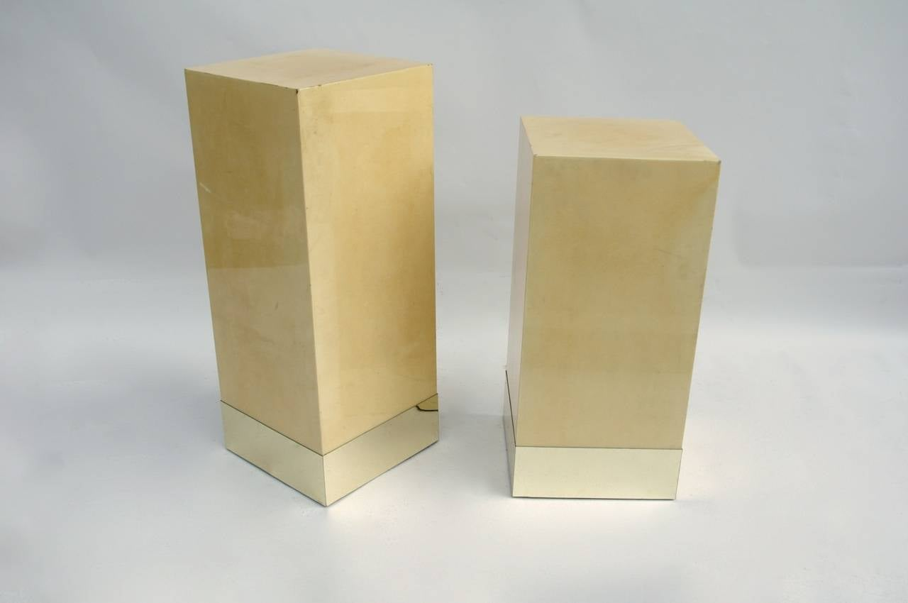 Pair of column side tables covered with parchment and standing on a gilt brass base. Made by Aldo Tura, italian designer, circa 1980.