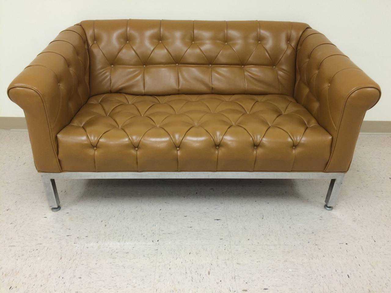 Signed Milo Baughman for Thayer Coggin tufted sofa in vinyl. Beautiful butterscotch color with chrome base, trim and legs. Perfect for office or home. Solid well built piece. Very good condition. Perfect for an office or modern bedroom.