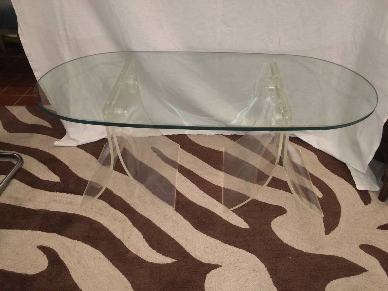 Lucite and glass coffee table. The glass top is 1/2 inch thick and the lucite bases can be placed in several different configurations. Perfect for small spaces with its airy open feel. Also easy to move from one room to another if needed.