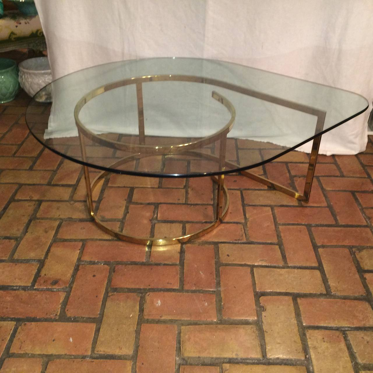 Hollywood Regency brass and glass coffee table. This elegant and sophisticated teardrop shaped table will complement any living room.