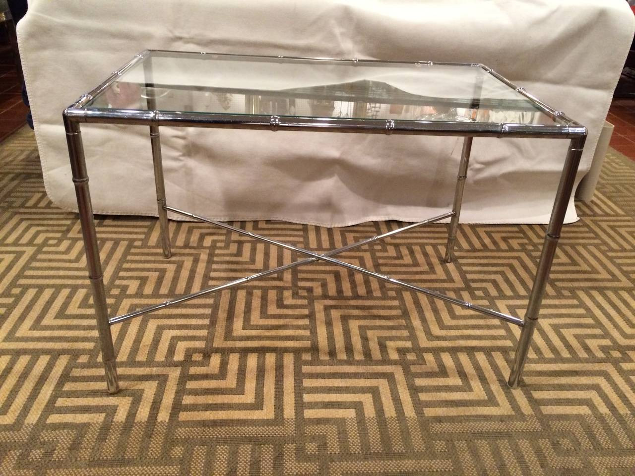 Milo Baughman Style Faux bamboo chrome and glass table with Classic X-base. This would fit in with any Hollywood Regency or Mid-Century Modern decor. Minimal clean lines make up this design.