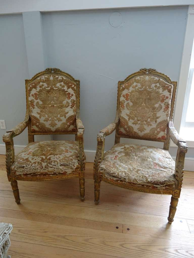 Pair of Louis XVI fauteuils. Elegant yet comfortable. In it's original woven velvet and silk tapestry upholstery. The pair need to be reupholstered but are heavy, sturdy chairs. Giltwood.