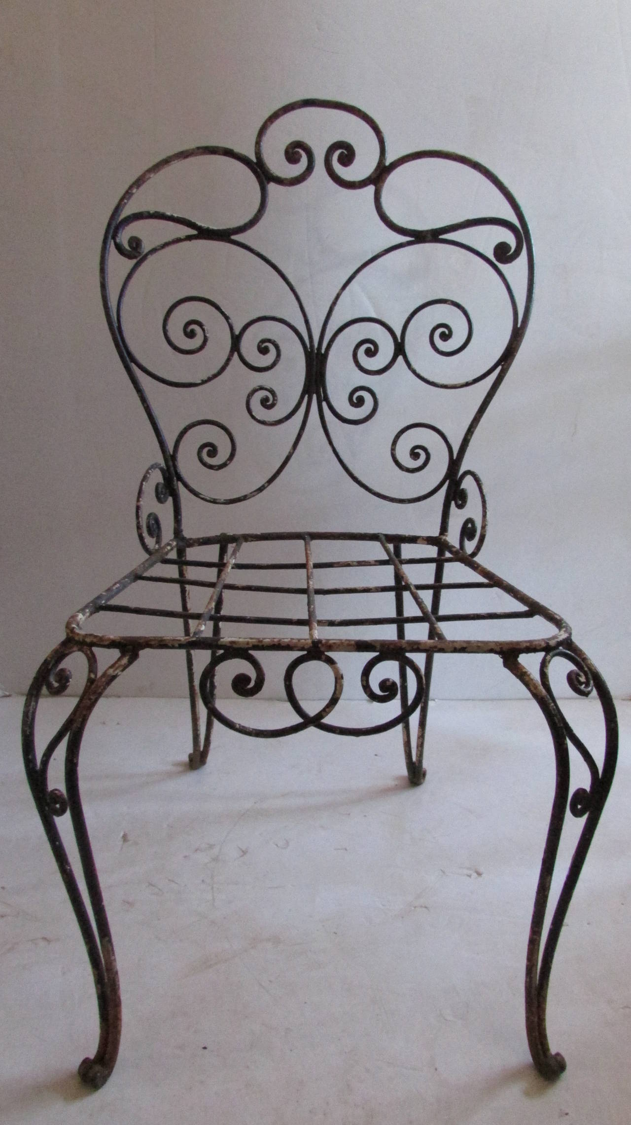 A very pretty antique iron garden chair with airy scrolled design and nicely aged worn black painted surface from years of outside use. Most likely French in origin - dating from the 1940's