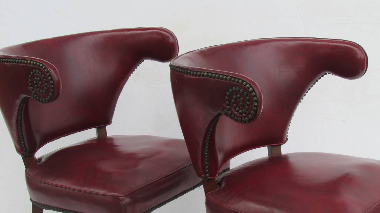 A beautifully tapered and sculptural pair of 1940's Regency exaggerated horseshoe back library chairs in old oxblood red leather like vinyl upholstery and all-over original  brass tacking. The carved fluted mahogany legs ending in fine brass rolling