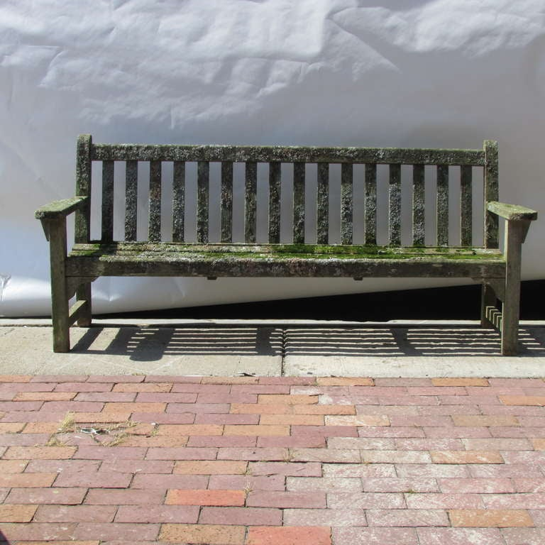 Teak garden bench in old weathered surface covered with moss and lichen from years of exposure to the elements.  High quality structurally solid heavyweight with pegged construction..