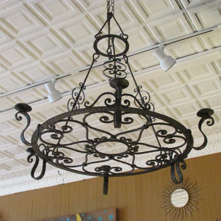 Early 20th century French hand forged iron chandelier with six candle armatures and beautifully detailed scrolled ironwork in nicely aged original surface. Initially designed for electric - presently not wired.