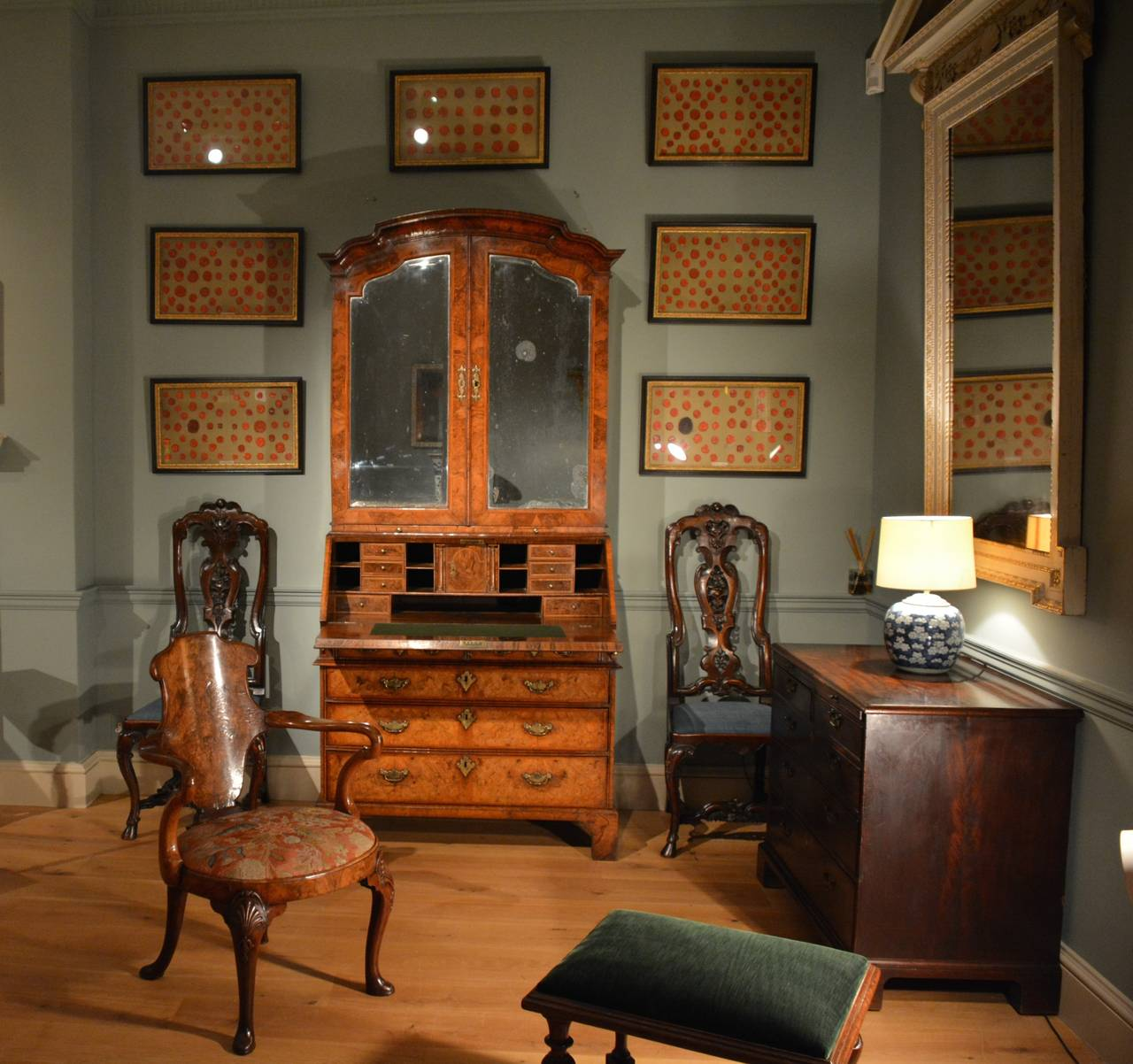 A fine quality early 18th Century bureau bookcase veneered throughout with burr walnut, having engraved brass mounts, the shaped cornice showing Chinese influence above a pair of shaped mirrored doors enclosing shelves to the upper section. The fall