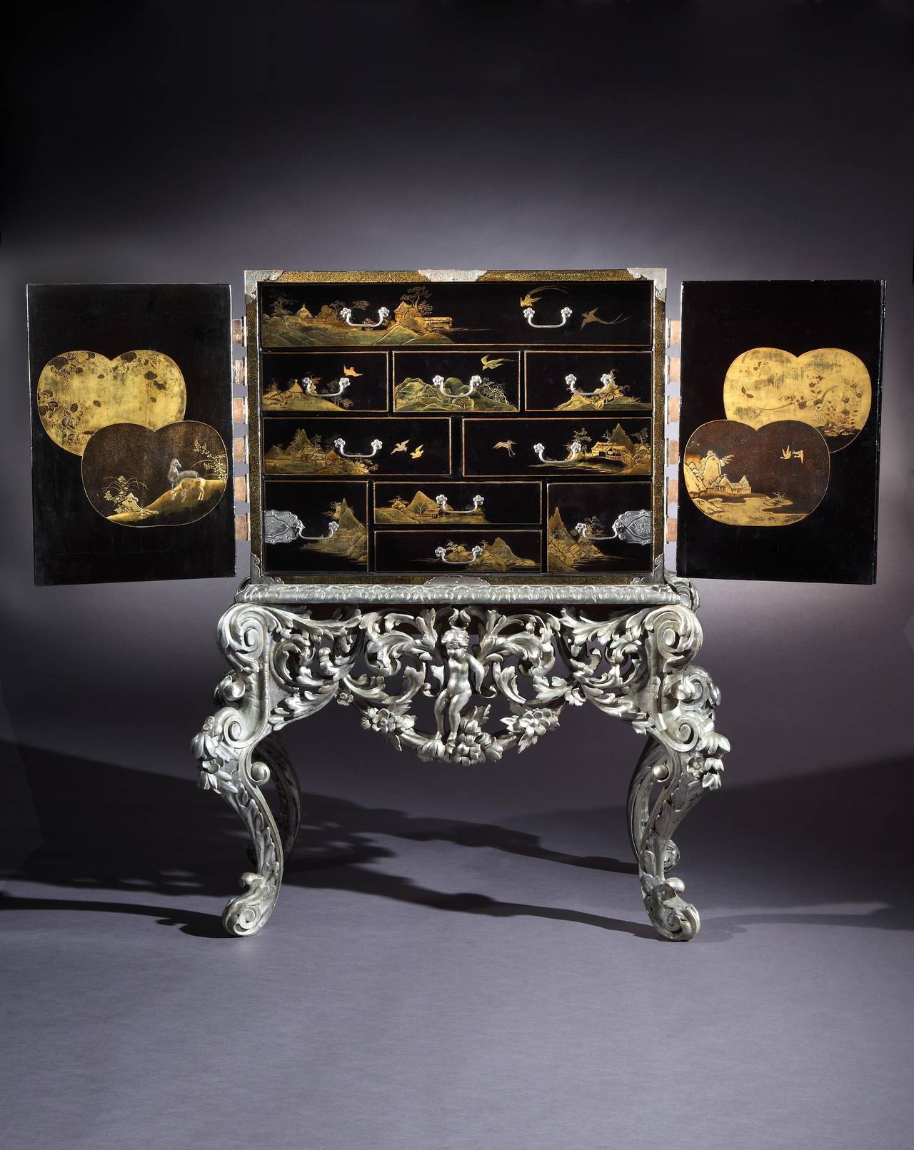 A fine late 17th, early 18th century silvered mounted Japanese black and gilt lacquer cabinet on a William and Mary silvered stand; the cabinet decorated throughout, including the top, with birds and pavilions within mountain landscapes, with a pair