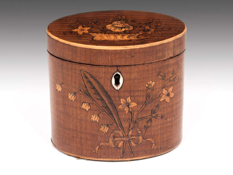 Miniature Harewood Oval Tea Caddy with floral pattern inlay on the front and top and bone escutcheon. The interior contains traces of its original lining and features a bone handle floating lid. This Tea Caddy comes with a fully working lock and