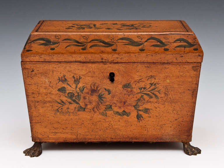 Penwork Tea Caddy with painted floral sprays, leaf pattern around its canted lid and stands on four lion pad brass feet.   The interior features two painted lid compartments with bone handles and still contains traces of the original lining.