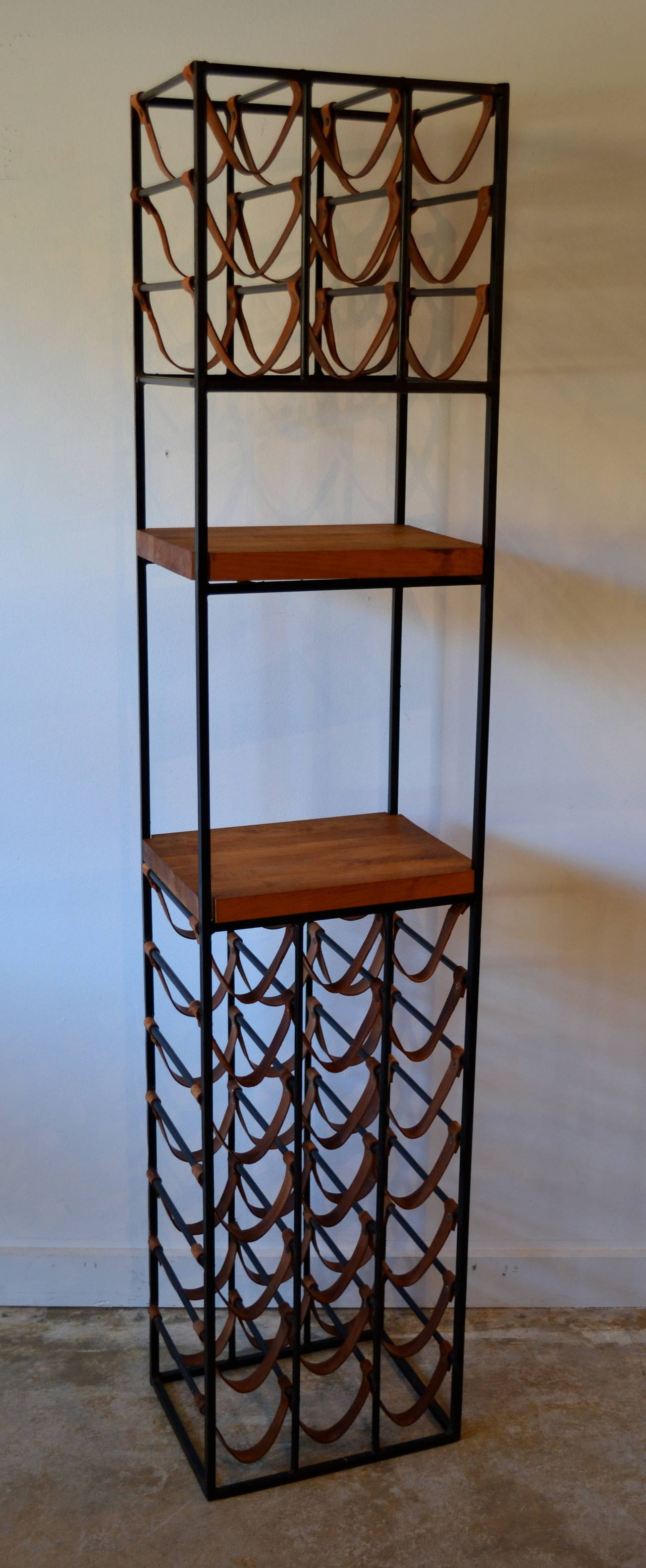 Two identical large tower wine racks by Arthur Umanoff, made of wrought iron with leather straps, two butcher block shelves for cutting or display, holds 30 bottles each.