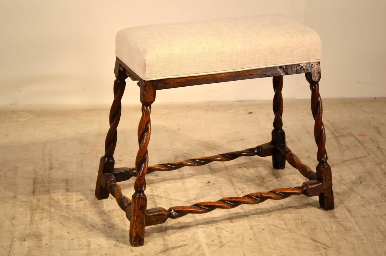 Extremely rare 17th century bench made from oak with a newly upholstered top in linen with single welt decoration. There is wear and signs of old repairs on the legs. Old woodworm damage as pictured. The seat measures 23.75 x 10.63.