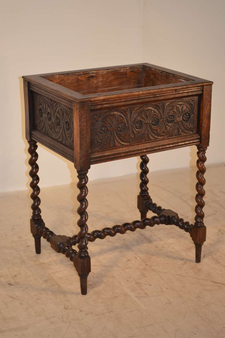 19th century English oak planter with lovely hand-carved panels on all four sides for easy placement in any room. Supported on wonderfully hand-turned barley twist legs, joined by a barley twit stretcher. Raised on tapered feet.