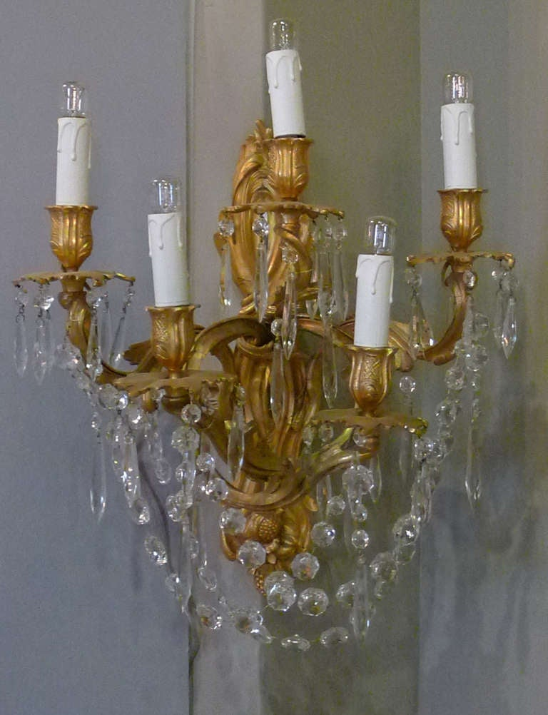 Fire gilded pair of wall sconces made in France. Hung with crystal and with five lights each.