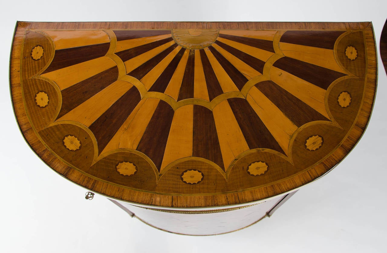 A fine and important George III period demilune Commode of rare small size and classical form, decorated with marquetry veneers of satinwood, tulipwood, harewood and other exotic timbers, enriched with cast and gilt metal mounts, in the manner of