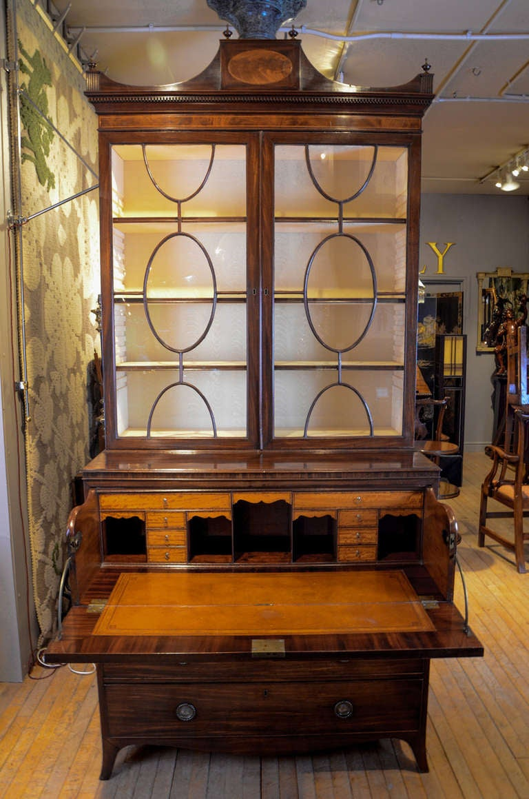 An important George III Secretaire Bookcase to designs by Thomas Sheraton, stamped on the three lower drawer linings by the maker, Lovell of Chichester. The upper part with swag shaped top cornice with central oval inlay of satinwood and six finials