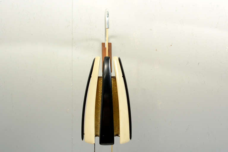 We are pleased to offer for your consideration a vintage Mid-century modern wall sconce.   It can be hung into the wall with the wood bracket. The aluminum arm can swing into different directions and it would allow to adjust the height of the