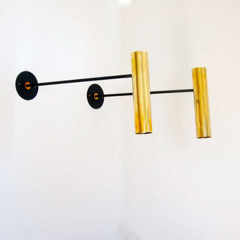 Sleek directional sconces by Boris Lacroix. Stem is fixed yet the brass shades move up and down, sideways and rotate in all directions. They are finished in an un-lacquered brass. Boris Lacroix was a French avant-garde designer influenced by fashion