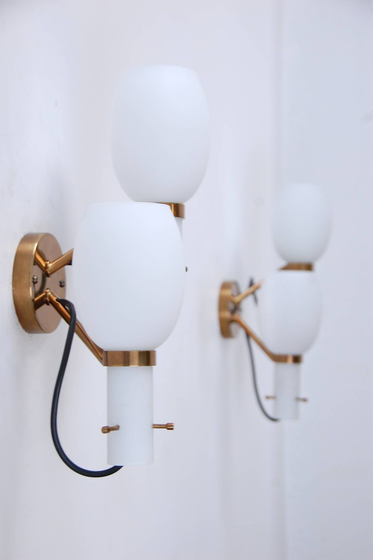 Graceful and stylish Stilnovo wall sconces from Italy. 1950s design with patina lacquered brass finish and handblown glass shades. Wired for use in the US.
