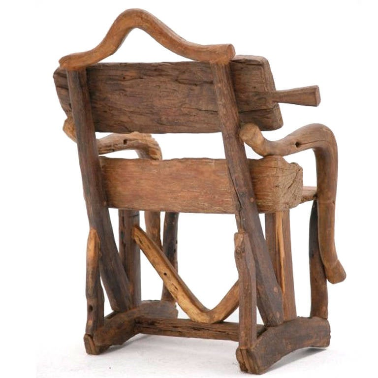 A sculpture of a chair in walnut and olivewood, handcraft and realized with remnants of old farm implements.