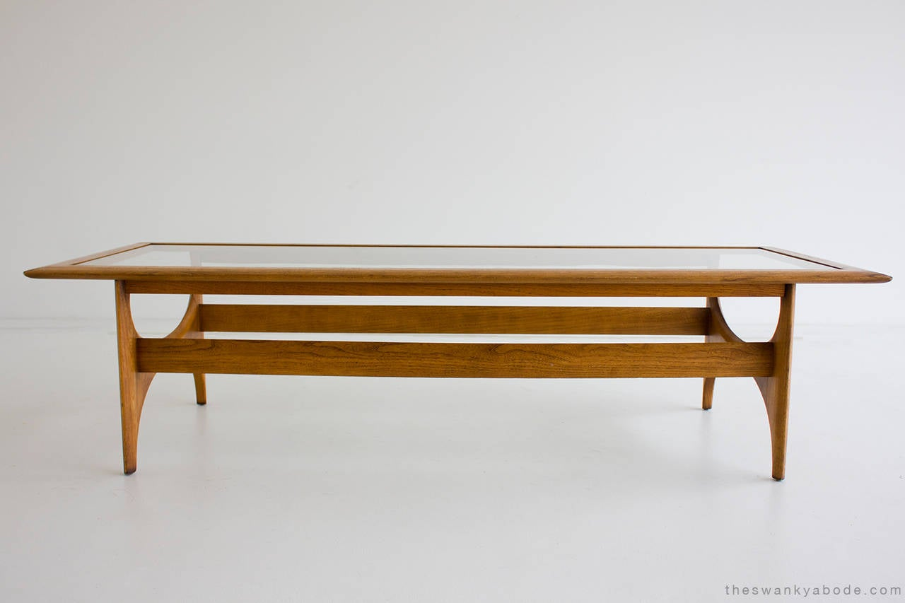 Designer: Unknown.  Manufacturer: Lane. Period and model: Mid-Century Modern. Specs: Wood, glass.  Condition:  This walnut coffee table for Lane is in very good vintage condition. The wood has normal wear with age consisting of dings nicks